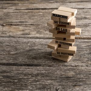Wooden pegs build in a tower with some of them reading words that represent the most important elements in the way towards success in business - vision, strategy, idea, innovation, plan and solution.